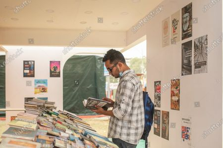 "A visitor reading through a book at a stall during the fair. Inaugurated by Prime Minister Sheikh Hasina, Amar Ekushey Book Fair-2021 in the capital at Bangla Academy and Suhrawardy Udyan will remain open till April. This year's book fair has been dedicated to the martyrs of 1971 Liberation War of Bangladesh. The main theme is ""Birth Centenary of Bangabandhu Sheikh Mujibur Rahman and Golden Jubilee of Independence""."