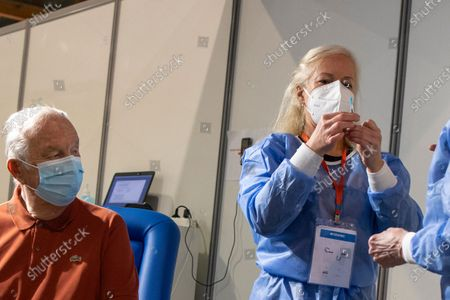Belgium's King Albert II, left, prepares to receive his COVID-19 vaccination at the Brussels Expo vaccine center in Brussels