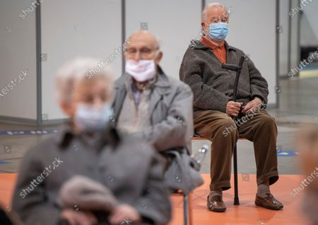 Belgium's King Albert II, rear center, sits in a waiting room after receiving his COVID-19 vaccination at the Brussels Expo vaccine center in Brussels