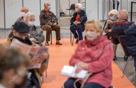 Belgium's King Albert II, rear left, and Queen Paola, rear right, sit in a waiting room after receiving their COVID-19 vaccinations at the Brussels Expo vaccine center in Brussels