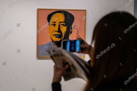 Stock Image of A Women takes a photo of a painting of Former Chairman of the People's Republic of China Mao Zedong inside the 'Not a Fashion Store' art exibition in Hong Kong, Thursday, March 18, 2021.