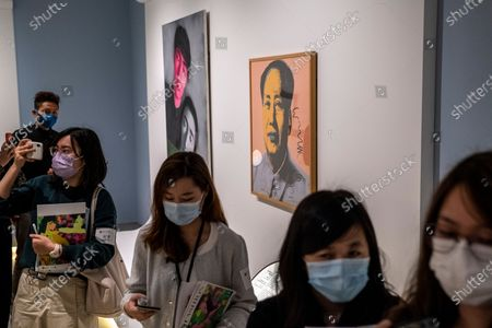 Stock Photo of People wall pass a painting of Former Chairman of the People's Republic of China Mao Zedong inside the 'Not a Fashion Store' art exibition in Hong Kong, Thursday, March 18, 2021.
