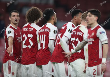 Arsenal players organise a wall, Granit Xhaka (left) instructs Hector Bellerin (right) to lay on the pitch