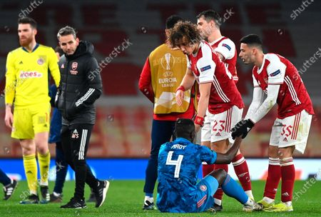 Olympiacos' Mohamed Camara (bottom) is comforted by Arsenal players David Luiz (C) and Gabriel Martinelli (R) after the UEFA Europa League round of 16, second leg soccer match between Arsenal FC and Olympiacos Piraeus in London, Britain, 18 March 2021.