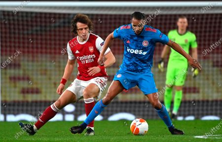 Olympiacos' Youssef ElArabi (R) in action against Arsenal's David Luiz (L) during the UEFA Europa League round of 16, second leg soccer match between Arsenal FC and Olympiacos Piraeus in London, Britain, 18 March 2021.