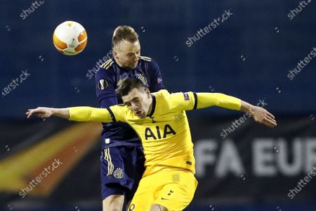 Tottenham's Harry Winks, bottom, jumps for the ball with Dinamo Zagreb's Sadegh Moharrami during the Europa League round of 16 second leg soccer match between Dinamo Zagreb and Tottenham Hotspur at the Maksimir stadium in Zagreb, Croatia