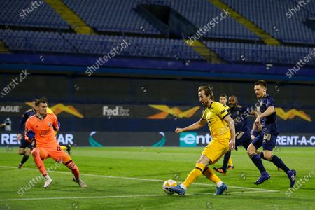 Tottenham's Harry Kane, right, attempts a shot at goal and misses in front of Dinamo Zagreb's goalkeeper Dominik Livakovic during the Europa League round of 16 second leg soccer match between Dinamo Zagreb and Tottenham Hotspur at the Maksimir stadium in Zagreb, Croatia