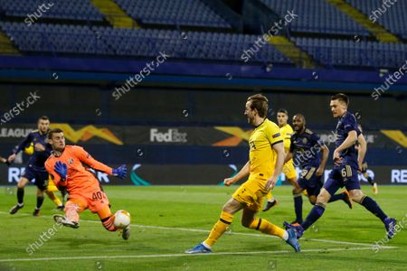 Dinamo Zagreb's goalkeeper Dominik Livakovic, left, makes a save in front Tottenham's Harry Kane during the Europa League round of 16 second leg soccer match between Dinamo Zagreb and Tottenham Hotspur at the Maksimir stadium in Zagreb, Croatia
