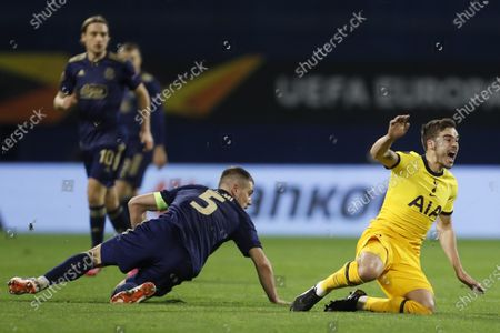 Tottenham's Harry Winks, right, reacts after a challenge by Dinamo Zagreb's Arijan Ademi during the Europa League round of 16 second leg soccer match between Dinamo Zagreb and Tottenham Hotspur at the Maksimir stadium in Zagreb, Croatia