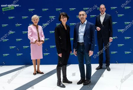 Ugur Sahin, second from right, and his wife Ozlem Tureci, second from left, the founders of the Mainz-based coronavirus vaccine developer BioNTech, are welcomed by publisher Friede Springer, left, and Mathias Doepfner, CEO of Axel Springer SE, at an Axel Springer Award ceremony for the research couple broadcast on the Internet