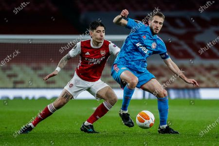 Olympiaco's Kostas Fortounis, right, duels for the ball with Arsenal's Hector Bellerin during the Europa League, round of 16, second leg soccer match between Arsenal and Olympiacos at the Emirates Stadium, in London