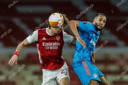 Arsenal's David Luiz, left, duels for the ball with Olympiaco's Youssef El-Arabi during the Europa League, round of 16, second leg soccer match between Arsenal and Olympiacos at the Emirates Stadium, in London