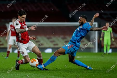 Arsenal's Hector Bellerin, left, duels for the ball with Arsenal's Gabriel during the Europa League, round of 16, second leg soccer match between Arsenal and Olympiacos at the Emirates Stadium, in London