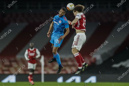 Olympiaco's Youssef El-Arabi, left, and Arsenal's David Luiz jump for the ball during the Europa League, round of 16, second leg soccer match between Arsenal and Olympiacos at the Emirates Stadium, in London