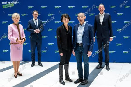 Ugur Sahin, second from right, and his wife Ozlem Tureci, second from left, the founders of the Mainz-based coronavirus vaccine developer BioNTech, pose for a photo while being welcomed by publisher Friede Springer, left, Austrian Chancellor Sebastian Kurz, second from left, and Mathias Doepfner, CEO of Axel Springer SE, at an Axel Springer Award ceremony for the research couple broadcast on the Internet