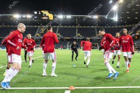 Ajax players Davy Klaassen (L), Nicolas Tagliafico (2-R), Ryan Gravenberch (R) and teammates warm up for the UEFA Europa League round of 16, second leg soccer match between BSC Young Boys and Ajax Amsterdam at the Wankdorf stadium in Bern, Switzerland, 18 March 2021.