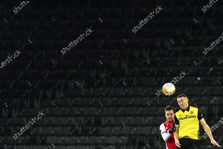 Ajax's Nicolas Tagliafico (L) in action against Young Boys' Silvan Hefti (R) in front of empty stands during the UEFA Europa League round of 16, second leg soccer match between BSC Young Boys and Ajax Amsterdam at the Wankdorf stadium in Bern, Switzerland, 18 March 2021.