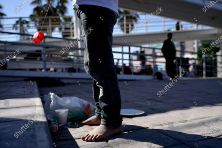 Stock Image of Luis Miguel Fajardo, 10, a migrant from El Salvador who was caught trying to sneak into the United States and deported, is barefoot as he plays with a yoyo at a plaza near a point of entry into the U.S., in Reynosa, Mexico. A surge of migrants on the Southwest border has the Biden administration on the defensive. The head of Homeland Security acknowledged the severity of the problem Tuesday but insisted it's under control and said he won't revive a Trump-era practice of immediately expelling teens and children