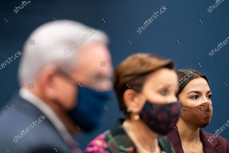 """Sen. Robert Menendez (D-NJ), left, and Rep. Alexandria Ocasio-Cortez (D-NY), right, listen as Rep. Nydia Velazquez (D-NY), center, speaks during a press conference to introduce the """"Puerto Rico Self-Determination Act of 2021"""" on Capitol Hill on Thursday, March 18, 2021 in Washington, DC. (Kent Nishimura / Los Angeles Times)"""