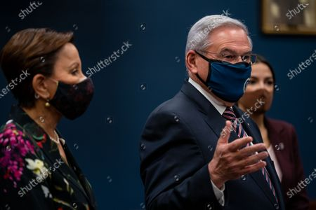"""Rep. Nydia Velazquez (D-NY) and Rep. Alexandria Ocasio-Cortez (D-NY), listen as Sen. Robert Menendez (D-NJ) speaks during a press conference to introduce the """"Puerto Rico Self-Determination Act of 2021"""" on Capitol Hill on Thursday, March 18, 2021 in Washington, DC. (Kent Nishimura / Los Angeles Times)"""