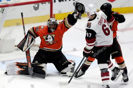 Anaheim Ducks goaltender Ryan Miller, left, uses his glove to make a save, as Arizona Coyotes left wing Lawson Crouse, right, collides with defenseman Jamie Drysdale during the third period of an NHL hockey game in Anaheim, Calif