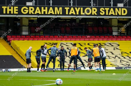 The Watford squad warms up in front of the Graham Taylor Stand before kick off