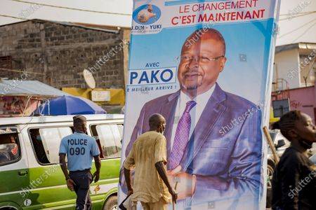 People walk past an election poster featuring opposition presidential candidate Guy Brice Parfait Kolelas in central Brazzaville, Congo, . Elections on Sunday March 21 will see President Denis Sassou N'Guesso poised to extend his tenure as one of Africa's longest serving leaders, 36 years, amid opposition complaints of interference with their campaigns