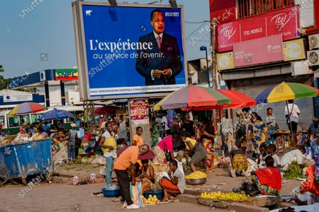 An election poster featuring President Denis Sassou N'Guesso stands over a market in central Brazzaville, Congo, . Elections on Sunday March 21 will see President Denis Sassou N'Guesso poised to extend his tenure as one of Africa's longest serving leaders, 36 years, amid opposition complaints of interference with their campaigns