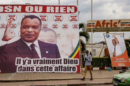 Man walks between election posters featuring opposition presidential candidate Guy Brice Parfait Kolelas, right, and President Denis Sassou N'Guesso, left, in central Brazzaville, Congo, . Elections on Sunday March 21 will see President Denis Sassou N'Guesso poised to extend his tenure as one of Africa's longest serving leaders, 36 years, amid opposition complaints of interference with their campaigns