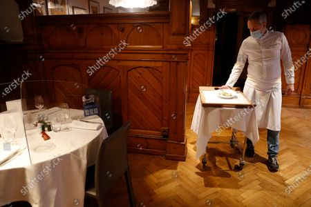 Stock Image of French Chef Eric Girardin, head of the Maison des Tetes restaurant, presents a dish after it was scanned under an ultraviolet scanning device used as a test to insure Covid-free food, in Colmar, eastern France. Eric Girardin is working a Covid-free restaurant while the French government announced Thursday a patchwork of new restrictions while reducing the national curfew by one hour. Restaurants, bars, cinemas, gyms, museums, theaters and concert halls have been shut down for almost five months, and will remain closed