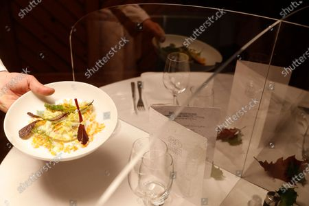 French Chef Eric Girardin, head of the Maison des Tetes restaurant, presents a dish after it was scanned under an ultraviolet scanning device used as a test to insure Covid-free food, in Colmar, eastern France. Eric Girardin is working a Covid-free restaurant while the French government announced Thursday a patchwork of new restrictions while reducing the national curfew by one hour. Restaurants, bars, cinemas, gyms, museums, theaters and concert halls have been shut down for almost five months, and will remain closed