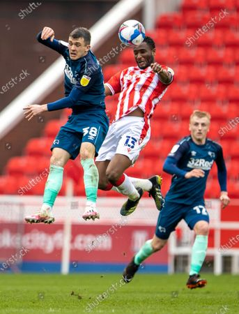 John Obi Mikel of Stoke City wins the header in front of Jason Knight of Derby County; Bet365 Stadium, Stoke, Staffordshire, England; English Football League Championship Football, Stoke City versus Derby County.