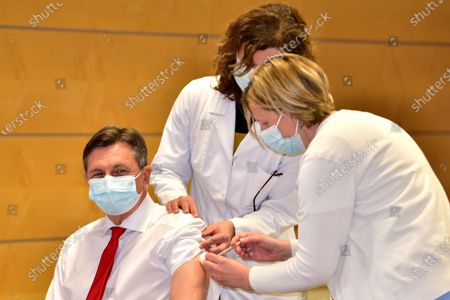 Slovenian President Borut Pahor (L) receives the first dose of the Oxford Astra-Zeneca COVID-19 vaccine in front of media at the NIJZ National institute of Public Health in Ljubljana, Slovenia, 19th March 2021. EU member countries reintroduce the AstraZeneca Covid-19 vaccine in their inoculation campaigns following the previous day's European Medicines Agency (EMA) announcement to uphold its approval of the vaccine. Some countries stopped giving the vaccine over fears there might be links between the vaccination against Covid-19 with the AstraZeneca vaccine and a rare number of blood clots.