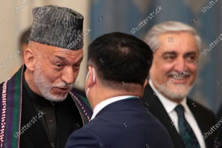 Former Afghan President Hamid Karzai, left, speaks to a member of Chinese delegation as and former Foreign Affairs Minister Abdullah Abdullah stands near prior to the opening of an international peace conference in Moscow, Russia, . Russia is hosting a peace conference for Afghanistan, bringing together government representatives and their Taliban adversaries along with regional observers in a bid to help jump-start the country's stalled peace process. The one-day gathering Thursday is the first of three planned international conferences ahead of a May 1 deadline for the final withdrawal of U.S. and NATO troops from the country, a date fixed under a year-old agreement between the Trump administration and the Taliban