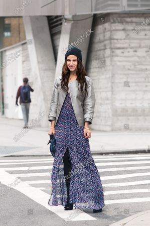 Nicole Fasolino stylist and art director, wearing beanie hat, gray metallic Emporio Armani jacket, Reformation floral maxi dress, Givenchy heels and Clare Vivier clutch bag. Nicole Fasolino