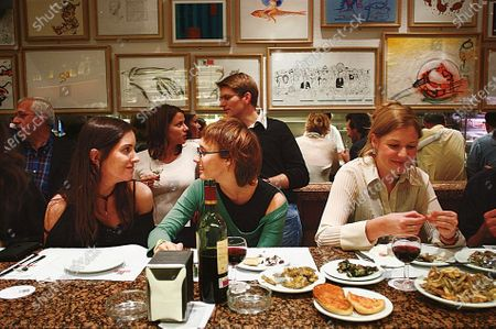 Diners seated at the counter of restaurant Cal Pep, eating and drinking wine, in Barcelona, Spain.