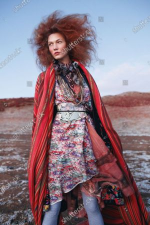 A desert sunset can go from purple to flaming pink, just like a ramble-ready frock. Karlie Kloss models an Etro floral dress, ruffled dress, and obi belt with Monique Péan Buffalo horn necklace, Ralph Lauren Home striped fabric (worn as wrap). Karlie Kloss
