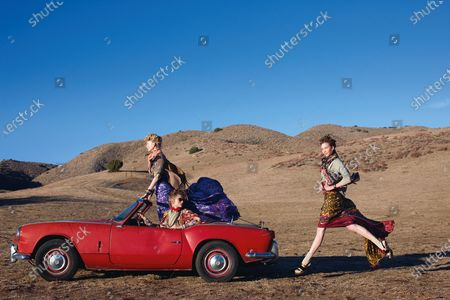 Three models with a red car in the desert, posing as fashionable nomads; From left: On Patricia van der Vliet: Lutz & Patmos cardigan, Dries Van Noten blouse and ikat skirt. On Abbey Lee Kershaw: Thakoon dress, Carlos Miele blouse. On Karlie Kloss: Dries Van Noten pullover and ikat skirt. Patricia van der Vliet, Abbey Lee Kershaw, Karlie Kloss