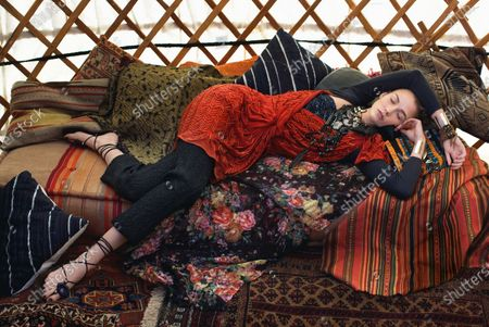 Stock Photo of Our Earth trekker, Karlie Kloss, takes respite in a yurt, wearing only the most beautifully embellished pieces. Lanvin scarlet beaded dress, Ann Taylor cashmere cardigan, Miu Miu cropped trousers, Catherine Malandrino agate necklace, Jimmy Choo clutch, and Jutta Neumann sandals. Karlie Kloss
