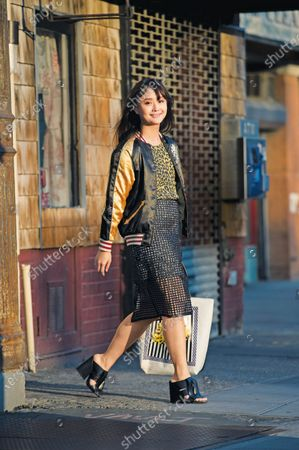Stock Photo of Connie Wang, of Refinery 29, wearing a black net pencil skirt from Banana Republic over a Rodarte for Target leopard lace dress topped with vintage silk jacket from Japan, and high heel Zara mules.