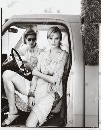 Stock Photo of A woman sits in the driver's seat of a truck, wearing a floral dress and a crocheted cardigan, with a man wearing a striped shirt and cowboy hat in the passenger seat. A fluttery chiffon number is dainty and dreamy but still practical (even for errands) when you pair it with casual flat sandals. For cool nights, crocheted cardigans with a handmade feel go well with down-home dressing. Dress, CK Calvin Klein. Sweater, Tracy Reese. Necklace, Oscar and Nancy at Pure Accessories. Bracelets, Roxanne Assoulin for Lee Angel. Sandals, Birkenstock.