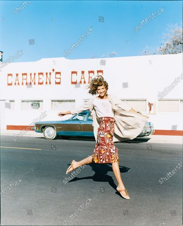 Stock Image of A woman in a Mexican patterned skirt, white top and long cardigan leaps in front of a café. A slim, flounce-free shape makes traditional Mexican prints look instantly modern. Wear a top that tucks in to show off a high waist. Skirt, and top, Nanette Lepore. Coat, Rebecca Taylor. Earrings, Roxanne Assoulin for Lee Angel. Sandals, Rafe.
