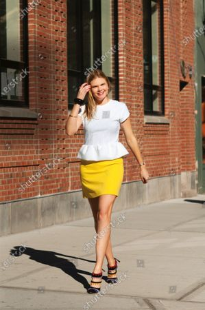 Kate Schelter, stylist, wearing a peplum top from Marc by Marc Jacobs with House of Lavande earrings, black lacquer bracelet, gold Tiffany & Co. bangle, yellow Ralph Lauren skirt and Manolo Blahnik high heels.