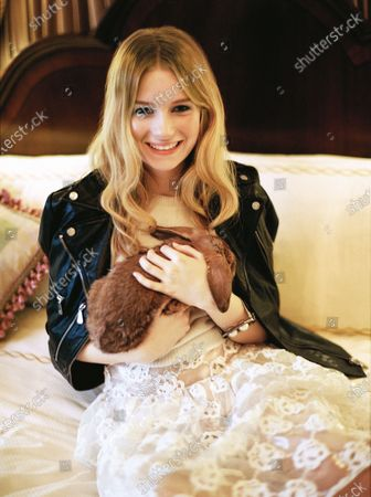 Lottie Moss holding a bunny rabbit and wearing a McQ Alexander McQueen jacket. Temperley London sweater. Simone Rocha skirt. Chanel bracelet. Lottie Moss