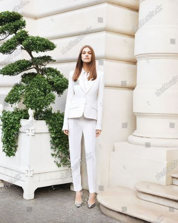 Model Samantha Gradoville wearing a white tuxedo by Pallas, standing next to a manicured topiary tree. Samantha Gradoville
