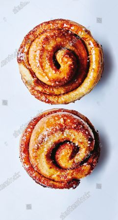 Two morning buns coated in honey butter and sprinkled with fine sanding sugar.