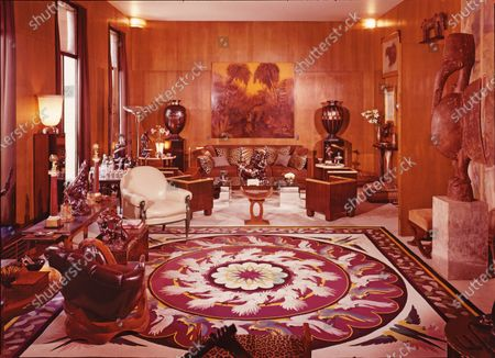 Stock Picture of The dramatic living room in Yves Saint Laurent's apartment in Paris on the left bank of the Seine, photographed in 1976. The rug is by Boisseau; Pierre Chareau chairs face Jean Dunand's enamel panel; vases are also by Dunand. At the center is a Jean de Bologne bronze; before it, a Pierre Legrain tabouret.