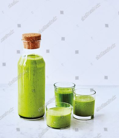 A carafe and three glasses of green gazpacho, a herbaceous summer soup.