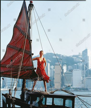Woman in a red dress stands on top of a boat, holding onto the sail. Does it swing, swish, swirl and move? Does its color knock you out? Then you've got the perfect fall '04 dress, like this one.