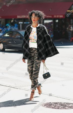 DJ Lindsey Caldwell wearing a plaid wool cape by Ralph Lauren with Pee-Wee Herman t-shirt, Moscot glasses, Chanel quilted handbag, A.P.C. camouflage pants, shoes by Melissa + Alexandre Herchcovitch high heels. Lindsey Caldwell